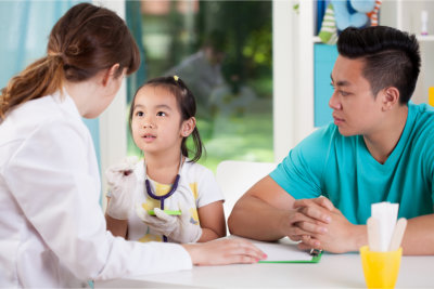 pediatrician interviewing on child with her parent